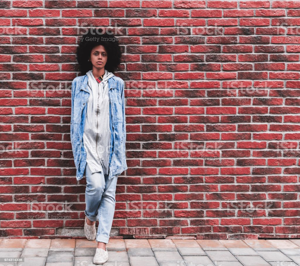 African-American female is leaning against a brick wall outdoors stock photo