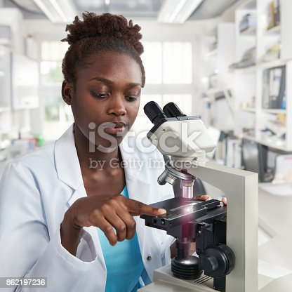 istock African-american female scientist, student or tech works with a microscope 862197236