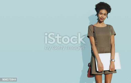 istock African-American female with laptop next to solid blue wall 956075944