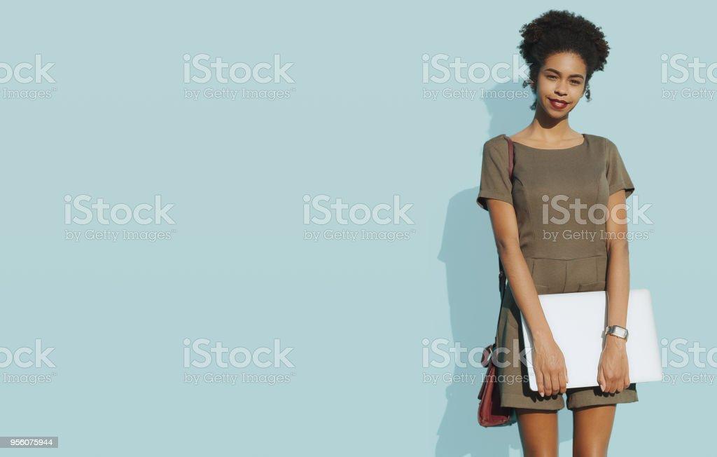 Afro-amerikanische Frau mit Laptop neben blauen Massivwand – Foto