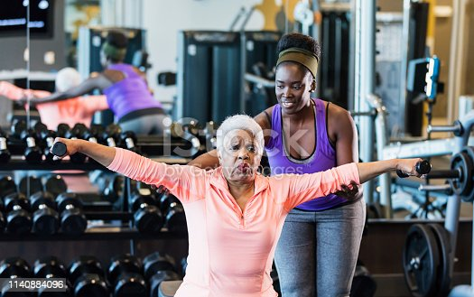 istock African-American fitness instructor helping senior woman 1140884096
