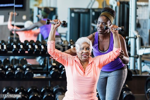 istock African-American fitness instructor helping senior woman 1172333856