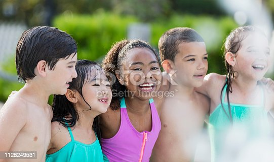 istock African-American girl and friends having fun at pool party 1128249531