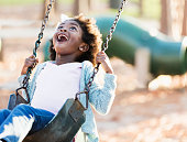 A 5 year old African-American girl playing on a playground, having fun swinging on a swing.
