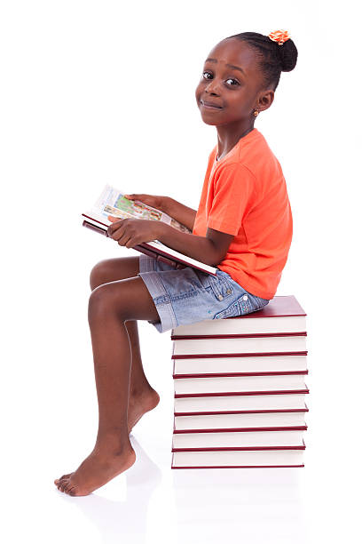 African-American girl reading atop stack of books stock photo