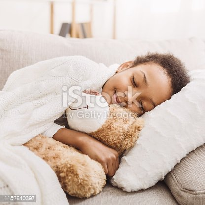 African-american girl sleeping with her toy in bed, crop