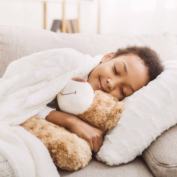 African-american girl sleeping with her toy in bed stock photo