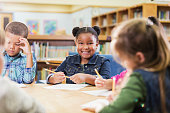 istock African-American girl with classmates at table, writing 1172284777