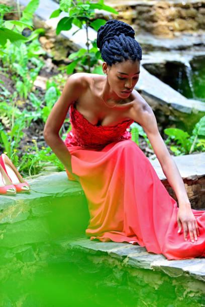 afroamerikanische mädchen mit dreadlocks auf ihrem kopf sitzt in einem roten kleid im sommer auf dem hintergrund der grünen pflanzen auf einem stein im park und glättet das kleid. - rote dreads stock-fotos und bilder