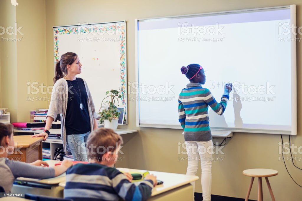 African-American girl writing on interactive whiteboard in classroom. royalty-free stock photo
