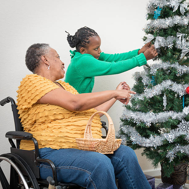 African-American granddaughter helping Grandmother Decorate Christmas tree stock photo