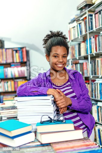 istock African-American high school girl with books in library 588367786