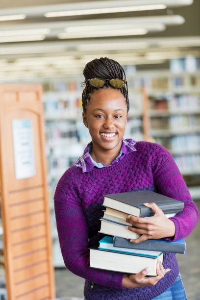 African-American high school student with stack of books A 15 year old African-American teenage girl in the library, carrying a large stack of books. She is a high school student working on a project. She is smiling at the camera, looking forward to her research. female high school student stock pictures, royalty-free photos & images