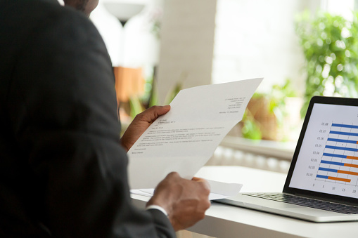 istock African-american hr employer reading cover business letter, over shoulder view 916520012