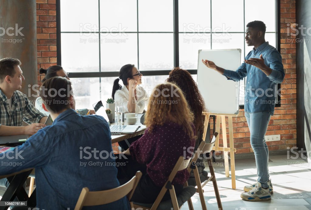 African-american leader lecturing his employees in office stock photo