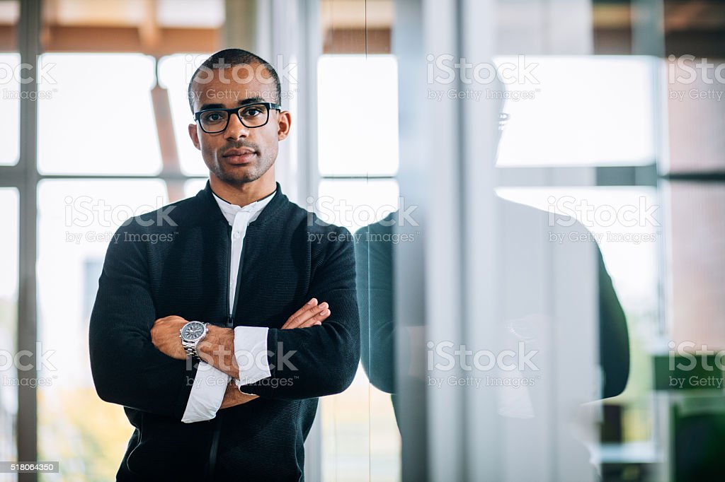 African-american leaning against office window stock photo