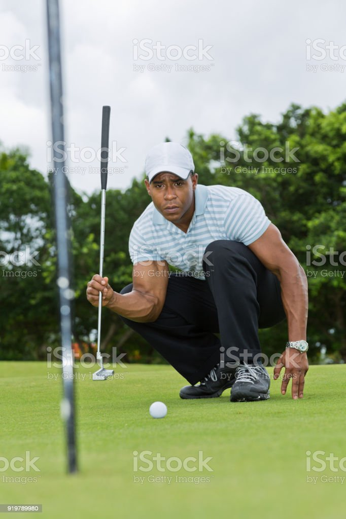 African-American male golfer reading the line stock photo