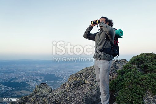 istock African-American male looking through binocular while standing on the hill top 959179824