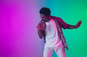 istock African-american male singer portrait isolated on gradient studio background in neon light 1226150009