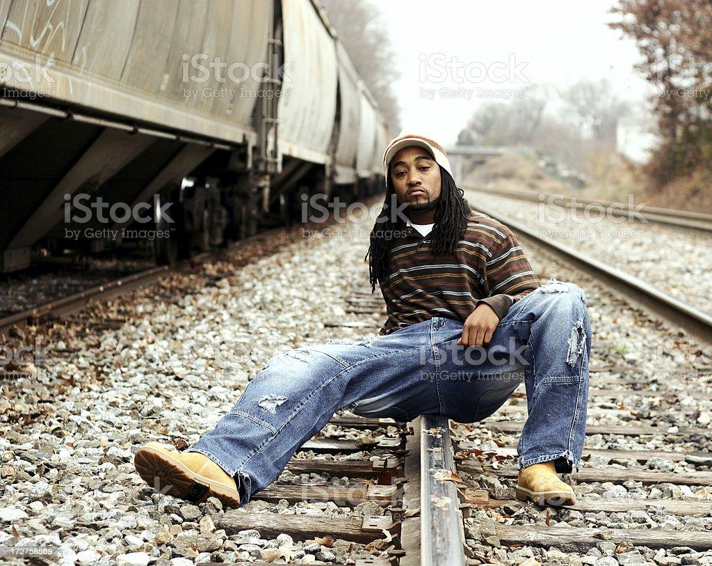 African-American male sitting on railroad rail