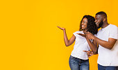 Cheerful Black Couple Is Pointing Away At Free Space, yellow background, panorama