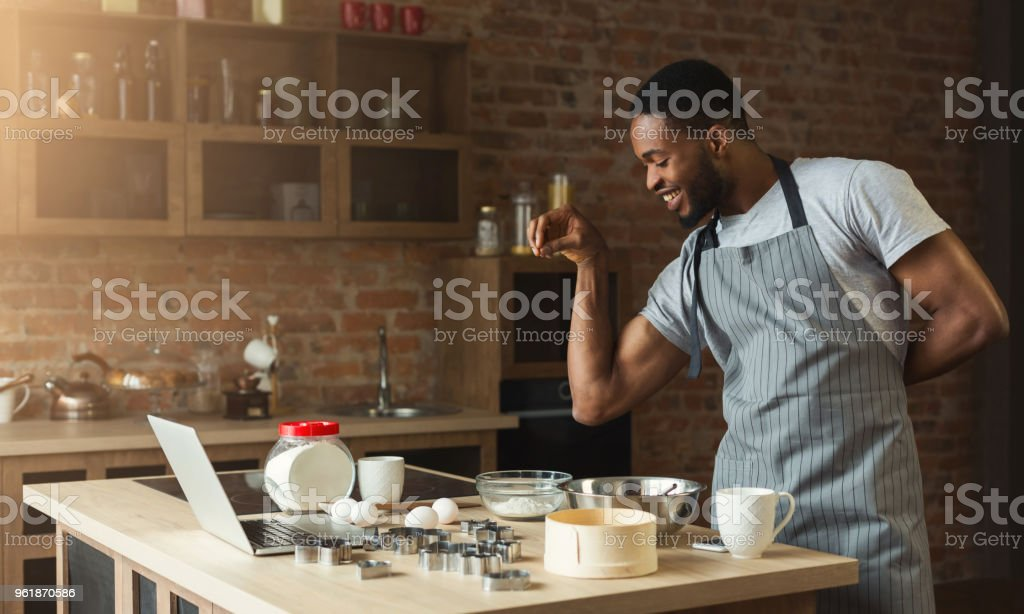 African-american man baking cookies at home kitchen stock photo