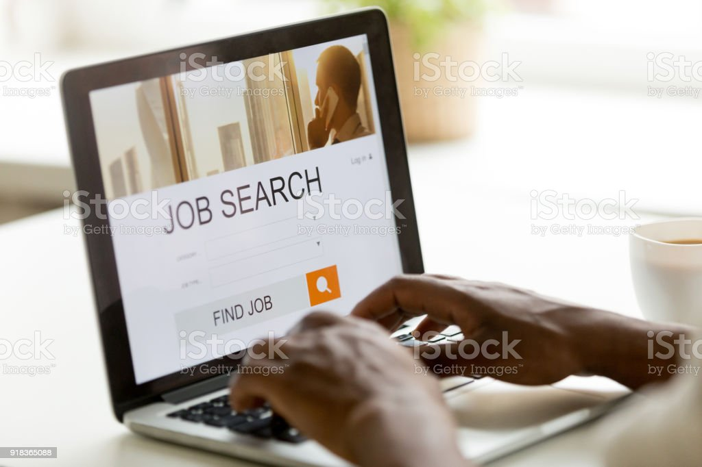 African-american man browsing work online using job search computer app stock photo