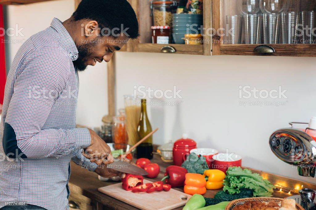 Afrikalı-Amerikalı adam kesme biber mutfak - Royalty-free Adamlar Stok görsel