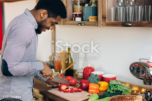 African-american man preparing delicious and healthy food in kitchen, cutting fresh vegetables, copy space