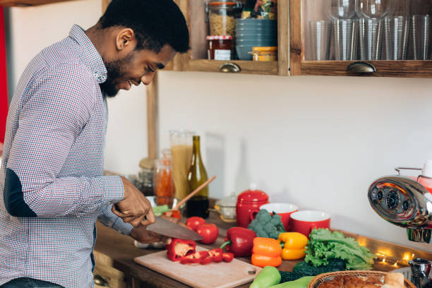 African-american man cutting bell pepper in kitchen African-american man preparing delicious and healthy food in kitchen, cutting fresh vegetables, copy space preparing food stock pictures, royalty-free photos & images