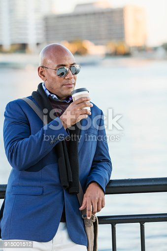 istock African-American man drinking coffee on city waterfront 915001512