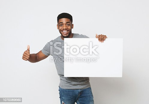 istock African-american man holding white blank board and showing thumb up 1070089560