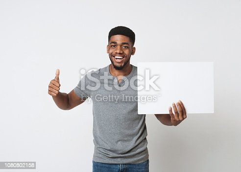 896826068 istock photo African-american man holding white blank board and showing thumb up 1080802158