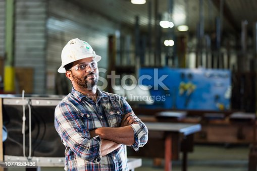 A mid adult African-American man in his 30s working in a manufacturing facility specializing in metal fabrication. He is wearing a hard hat and safety goggles.