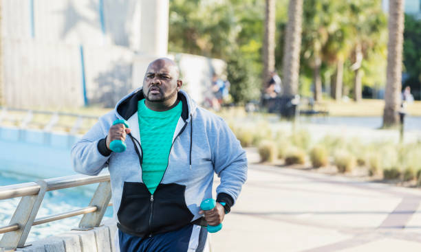 African-American man jogging or power walking A mature African-American man in his 40s with a large build, exercising outdoors in a city park. He is wearing a fitness tracker, jogging or power walking with hand weights. body positive stock pictures, royalty-free photos & images