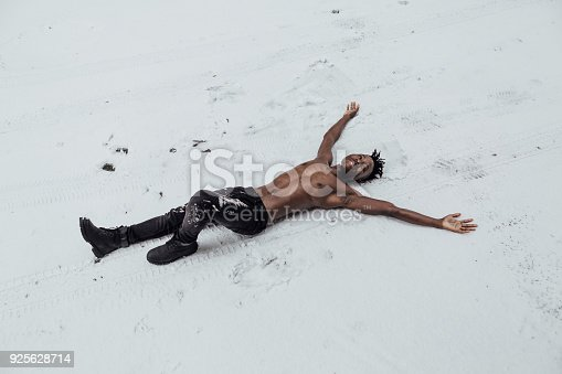 istock African-American man lies on the snow 925628714