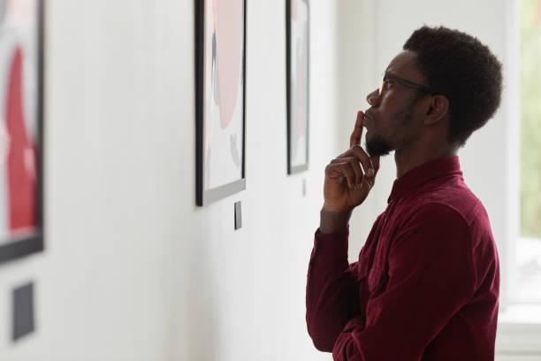 African-American Man Looking at Modern Art stock photo