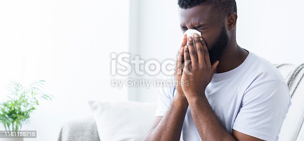 Unhappy black millennial guy suffering from snots, blowing his nose at home, panorama with empty space