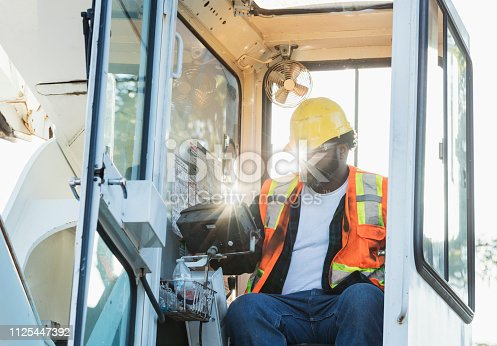 An African-American man in his 30s working as a crane operator at a construction site.  He is sitting in the cab of the vehicle wearing a hardhat, reflective vest and safety glasses.