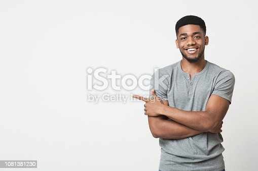 istock African-american man pointing aside at copy space 1081381230