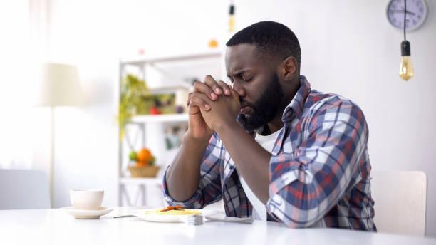 afroamerikanischer mann betet vor dem mittagessen und dankt gott für essen, religion - gott sei dank stock-fotos und bilder