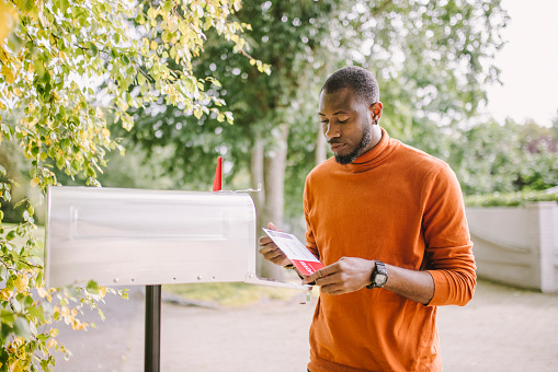 Portrait of African-American man receiving mail-in voting ballot.
