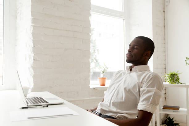 African-american man relaxing after work breathing air in home office stock photo