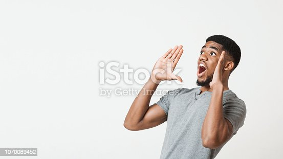 istock African-american man screaming with excitement, copy space 1070089452