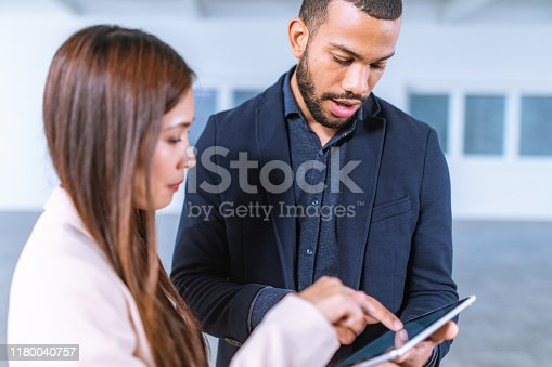 istock African-American man showing something on digital tablet to Asian colleague 1180040757