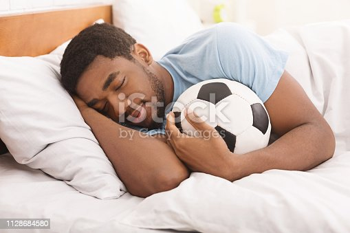 istock African-american man sleeping and embracing soccer ball 1128684580