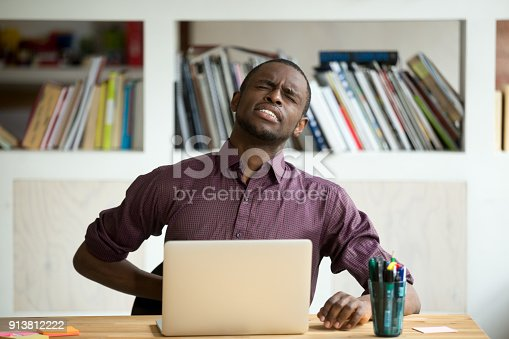 istock African-american man touching back sitting at desk feeling sudden backache 913812222