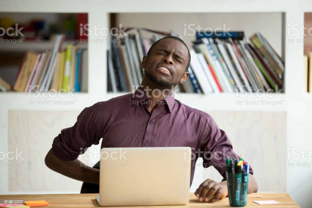African-american man touching back sitting at desk feeling sudden backache stock photo