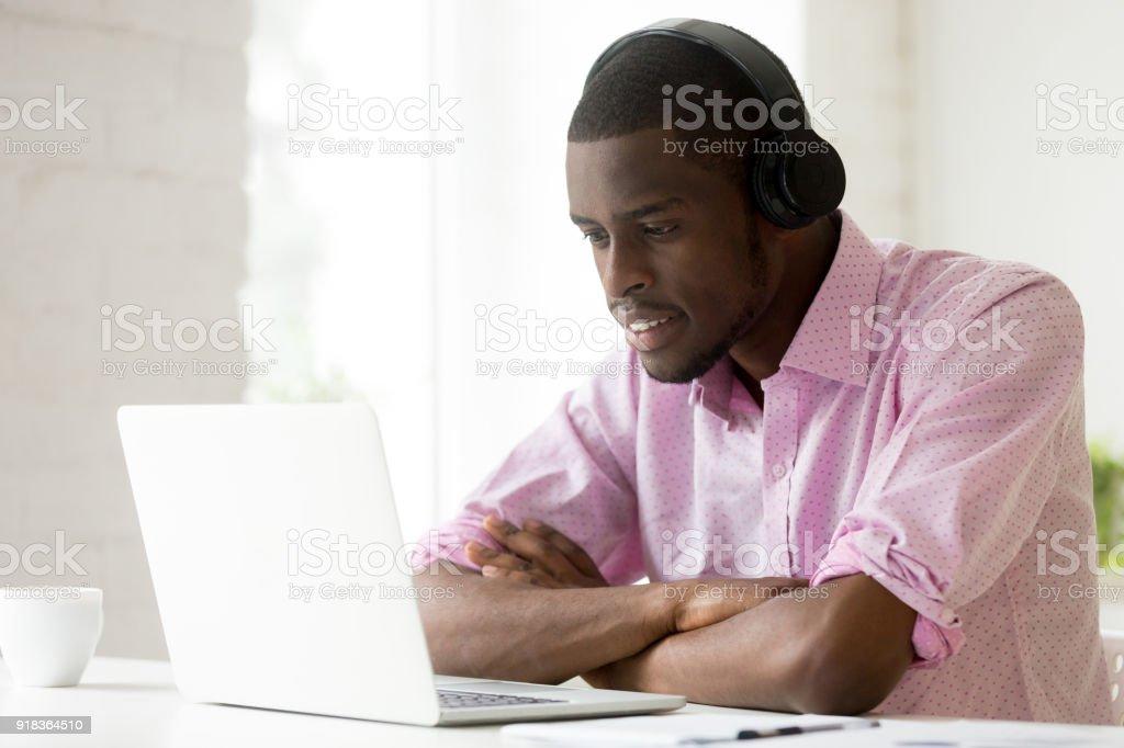 African-american man wearing headphones using laptop looking at computer screen stock photo