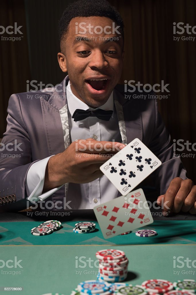 African-american man winning at the poker table stock photo
